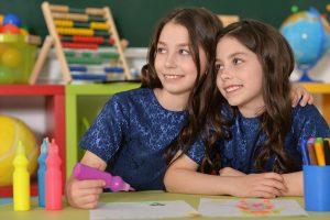 irmãs gêmeas juntas na escola